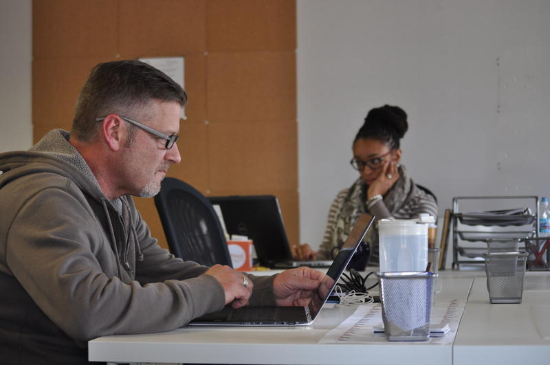 Dean Puckett (left), a federal navigator, and Ashlei Howard, a certified application counselor, sit in their new offices at the St. Louis Effort for AIDS just two days before the start of open enrollment season.