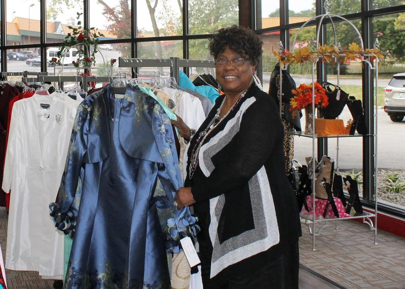 Owner Juanita Morris shows off a new dress at the recently reopened Fashions R Boutique.