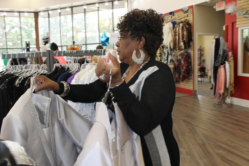 Fashions R Boutique owner Juanita Morris sets out merchandise in her new Florissant location, after her original store burned in the riots following the Darren Wilson grand jury decision in November 2014.