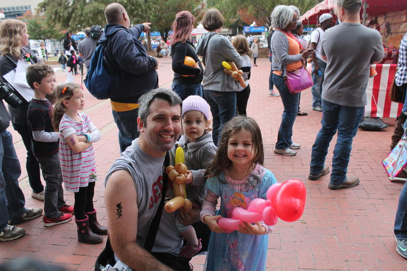 Jeff, Madeline and Alexis Smith of Ballwin enjoy balloon animals at Arch 50 Fest.