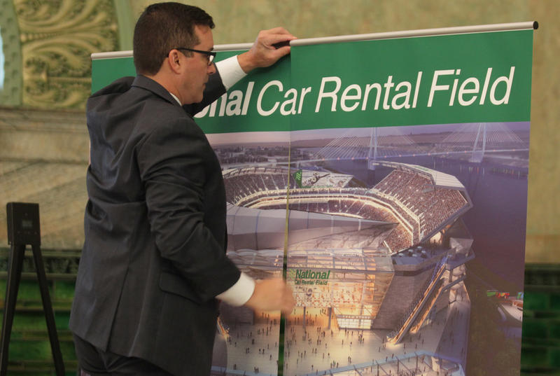 A member of the St. Louis stadium task force, places signage in the room before the announcement that National Car Rental has agreed to pay $158 million over 20 years for naming rights for the proposed NFL stadium in St. Louis on October 7, 2015.