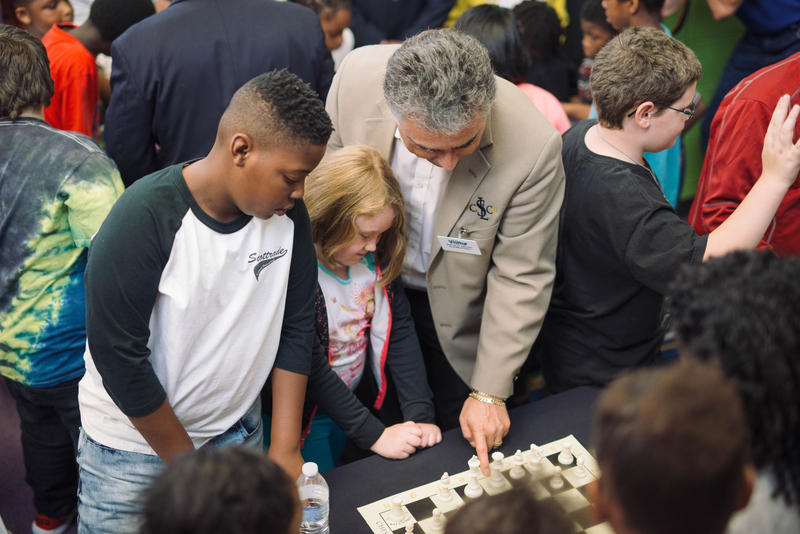 Kids crowd a chess board at the announcement of the Ferguson-Florissant schools program.