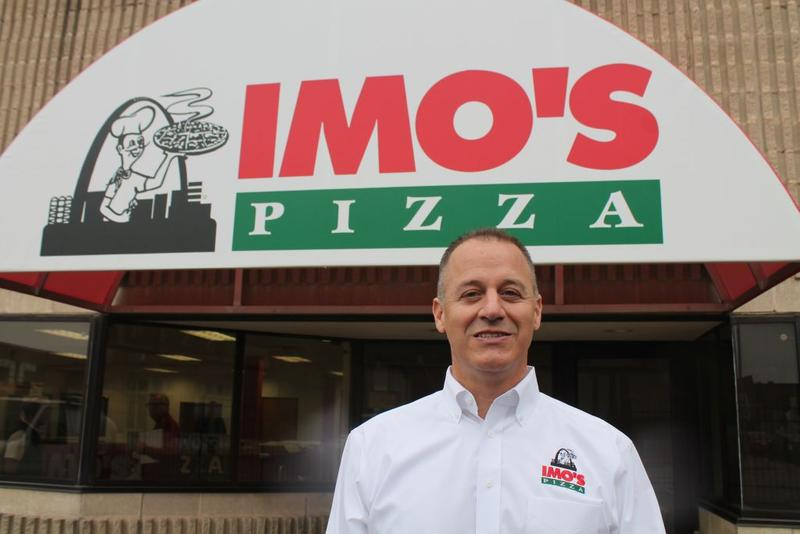 Carl Imo, son of the local pizza staple's founders Ed and Margie, stands in front of the company's new headquarters downtown wearing a shirt with the logo: a chef holding a steaming hot pizza against the Arch and downtown skyline.