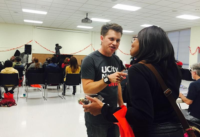 UCityNeeds.me director Chris Paavola, (left), speaks with a resident during a results party Saturday at the Heman Park Community Center. Paavola and other University Center organizers launched a campaign to link residents with causes they care about.