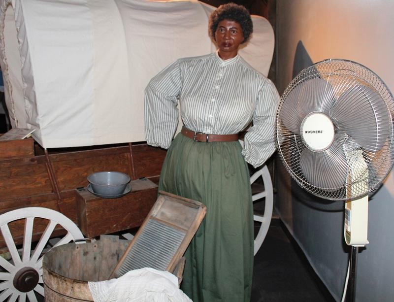 A modern-day fan seems out of place in Clara Brown's 1859 wagon train scene. Fans help cool the museum since three of the four air conditioning units were damaged by vandals.