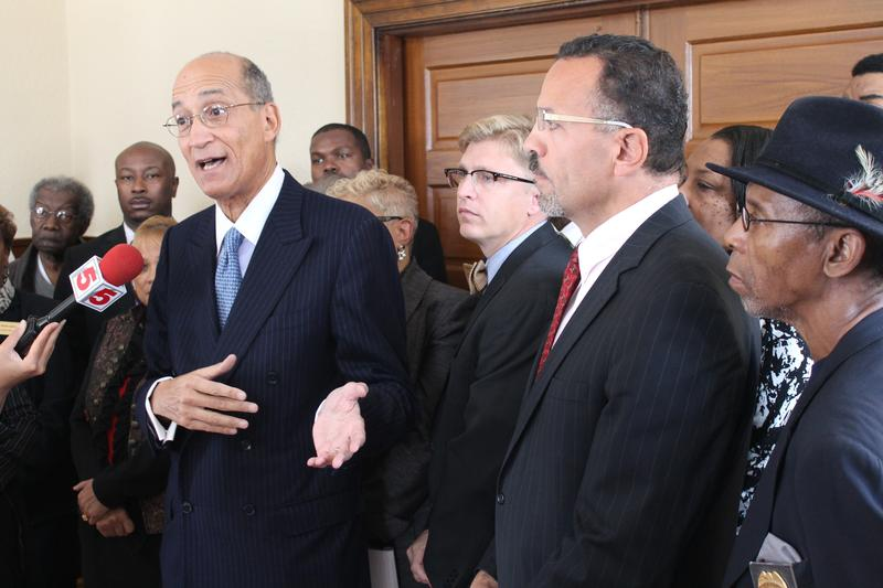 Attorney David Pittinsky stands with mayors of numerous St. Louis County cities on Thursday. Pittinsky is leading a lawsuit against a state municipal overhaul.