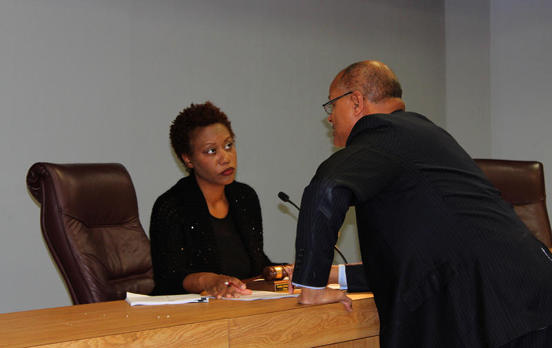 East St. Louis City Manager Alvin Parks leans over the city council table Thurs. Nov. 12, 2015 to speak to Mayor Emeka Jackson-Hicks.