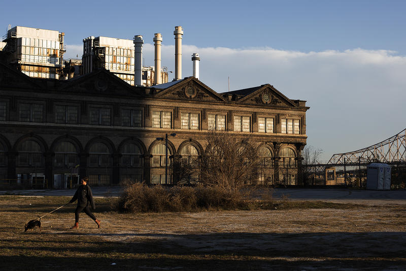 Grace Kenyon walks her dogs, Lhenny and Brown, near the Ashley Street Power House, a city landmark that developers have said could become a team store in the proposed stadium plan.