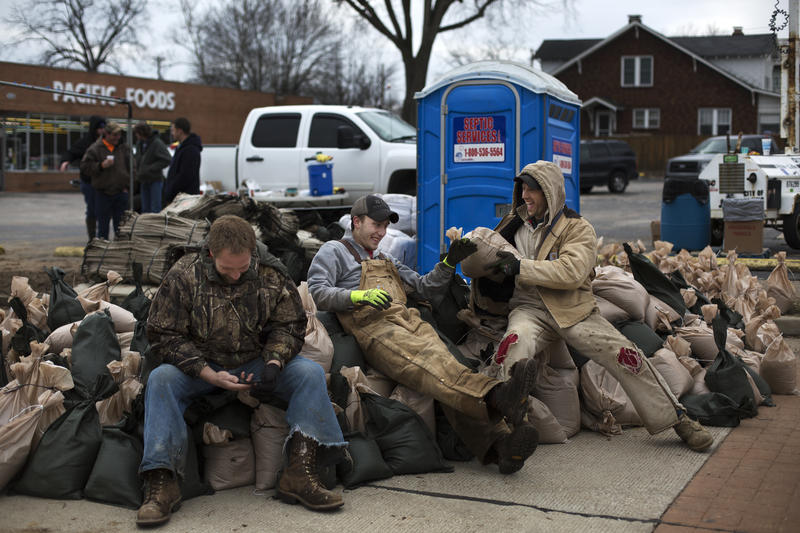 Volunteers Mike Miles, James Kurtz and Clint Beckerdit rest atop sandbags they helped fill in Pacific Wednesday afternoon, Dec. 30, after finding out the river had just crested. The group had been filling sandbags since Sunday afternoon.