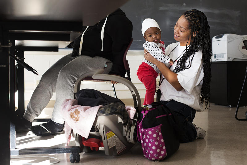 Sparkle Burns, a community coach with Jobs Plus, entertains Kylie Short while the 9-month-old's mother works on her resume at Clinton-Peabody's Al Chappelle Center in December 2015.