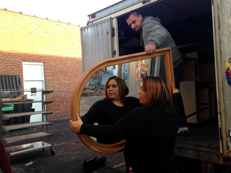 Jamie Stevens (center) unloads a mirror at the donation center with Ferid Keranovic (top).