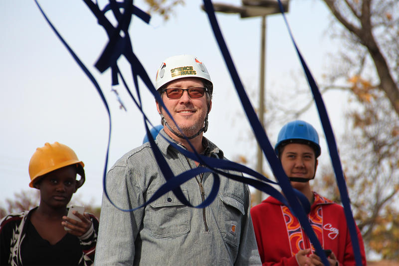 Bill Henske, a seventh grade science teacher at Maplewood Richmond Heights Middle School, smiles as students climb an Oak tree. Students use their cell phones to time the how long it takes for objects dropped from the top of the tree to hit the ground.