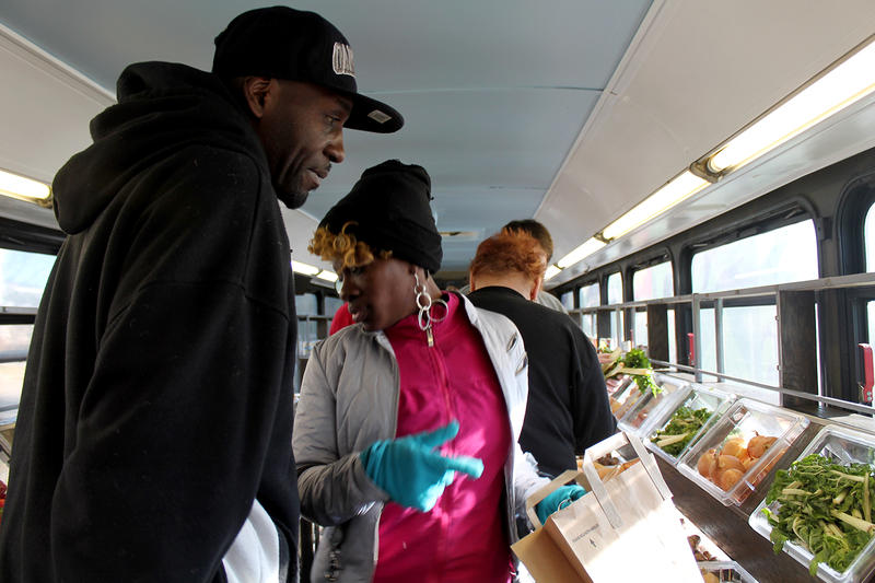 Richard Claston and Jessica Graham pick up ingredients for sweet potato chili inside the retrofitted Metro bus turned into a mobile farmers market in St. Louis' JeffVanderLou neighborhood Sat. Dec. 19, 2015.