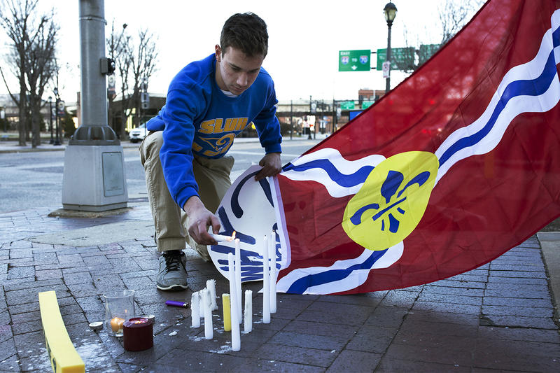 "Sam Sextro lights candles across the street from the Edward Jones Dome while mourning the city's loss of the Rams. Sextro and a friend, who ran a St. Louis University High Rams fan club, met outside the stadium Wednesday for a ""final tailgate."""
