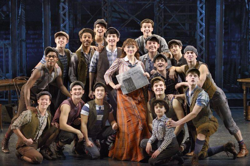 The newsies including Alex Prakken, kneeling on the right behind the small boy, surround Jack's love interest, Katherine