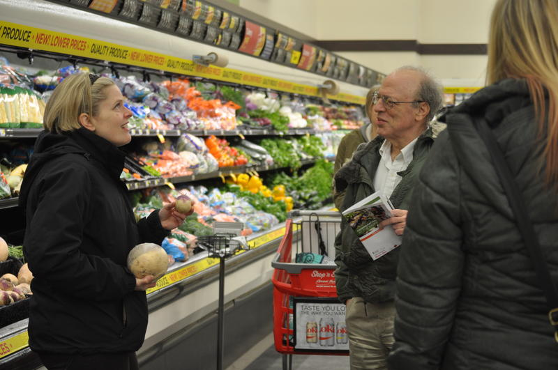 Christina Popp of Operation Food Search extolls the virtues of turnips and rutabagas on a Cooking Matters in the Store tour at a Ferguson Shop 'n Save. Steve Weisman of St. Louis County looks on.