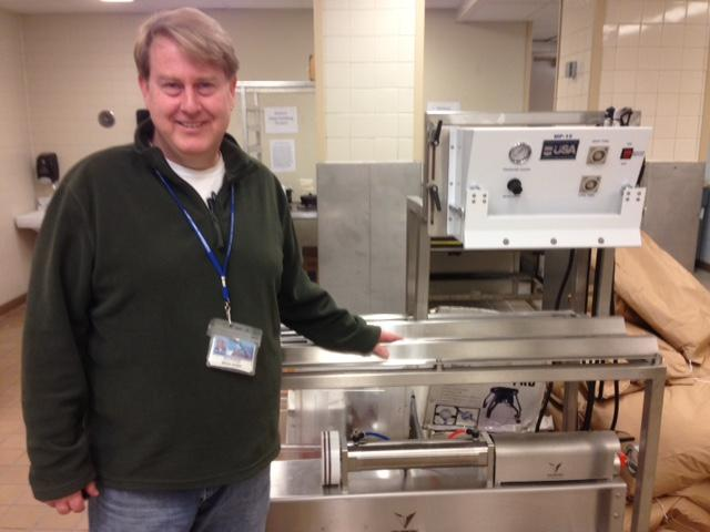 Steve Jenkins is an assistant professor and director of the food innovation and entpreneurship program. He's standing next to a new hot-fill unit that will allow the kitchen to bag perishable foods like marinara and applesauce and shelve it.