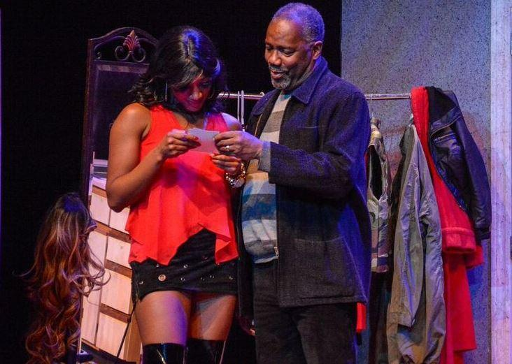 Erin Renée Roberts as Nina and Ron Himes as Kenyatta look at photographs of Nina's late mother in the Black Rep's