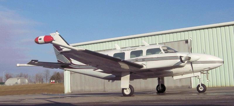 The USGS will collect data on mineral deposits in the St. Francois Mountains using a Piper Navajo airplane with auxiliary wingtip pods and tail stinger magnetometers.