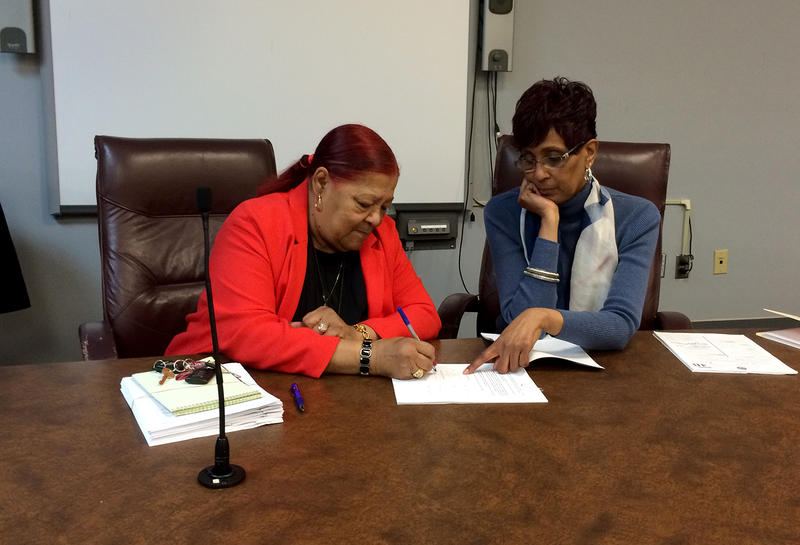 Edith Moore, interim city manager for East St. Louis signs an ordinance under the direction of City Clerk Dorene Hoosman on Mon. Jan. 4, 2016.