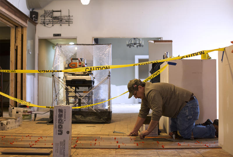 Mike Weber puts down new flooring in front of the bar at the Pacific Brew Haus on Wednesday, Feb. 3, 2016. The bar and restaurant, which occupies the first floor of the historic McHugh-Dailey building, was damaged by flooding in late December.