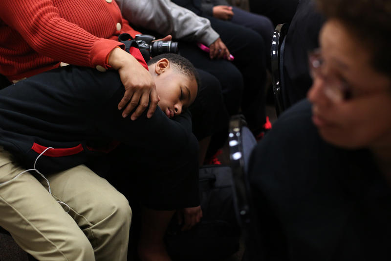Eleven-year-old Gabriel Cornelius rests on his mother's lap as city council members address residents' questions.