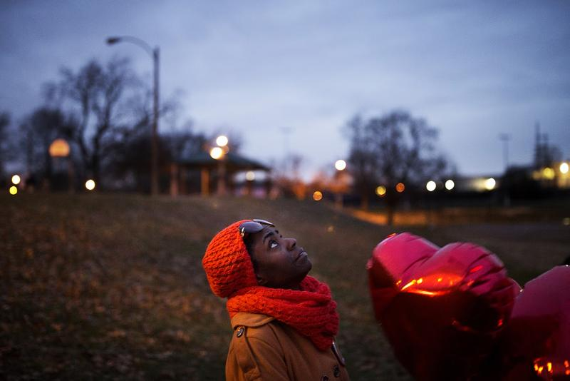 Renee Whitfield looks up as she releases heart-shaped balloons in memory of her son, Rashad Farmer, who was fatally shot last July.
