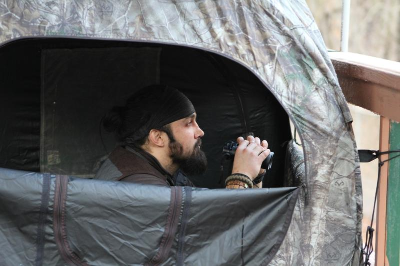 Observer Matt Fox hunkers down in a wolf blind outside the enclosure for red wolves.