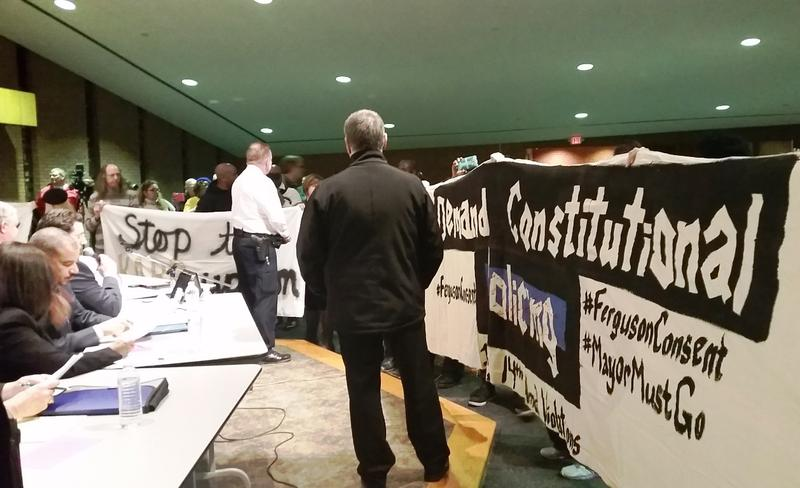 Protesters carrying a banner that reads demand constitutional policing work to interrupt a meeting of the Ferguson City Council on February 23, 2016.