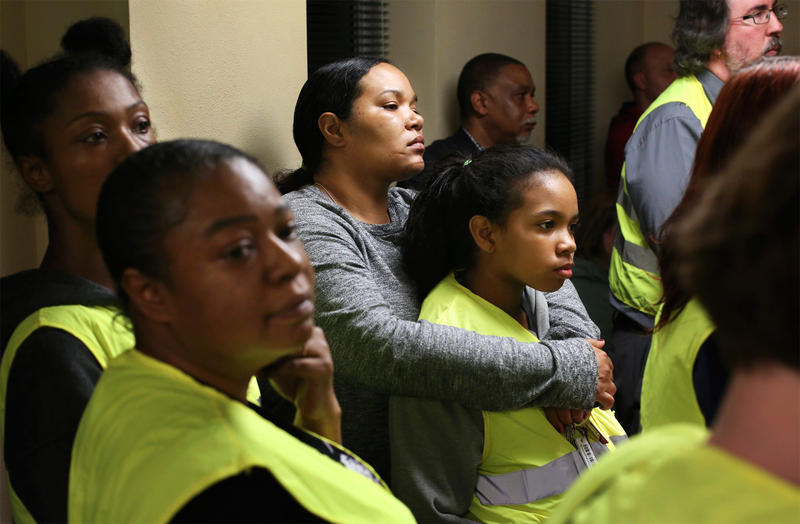 A group of more than a dozen activists, including Francesca Griffin and Mauraye Love, 9, center, wore bright safety vests and silently interrupted the council meeting to call on the city to agree to the Department of Justice's proposed consent decree.