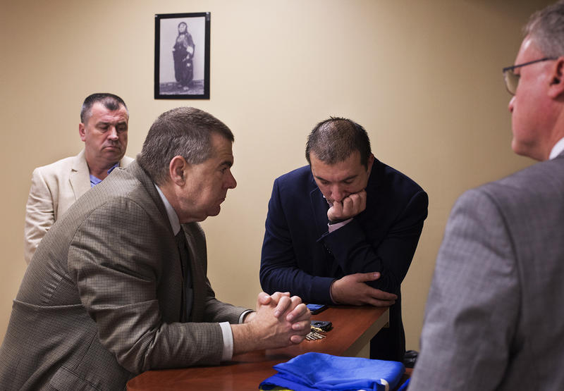 Sadik Kukic, far left, Benjamin Moore, Akif Cogo and Patrick McCarthy listen to a live stream of Radovan Karadzic's verdict while gathered at the Bosnian Chamber of Commerce on Gravois Avenue.