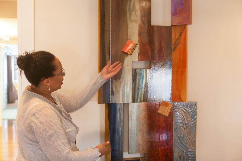 Adrienne Davis with a work by Sam Gilliam. It is acrylic on polypropylene on birch panels.