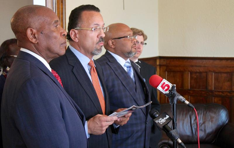 Normandy Mayor Patrick Green, center, speaks to the media after a judge struck down numerous aspects of SB5.
