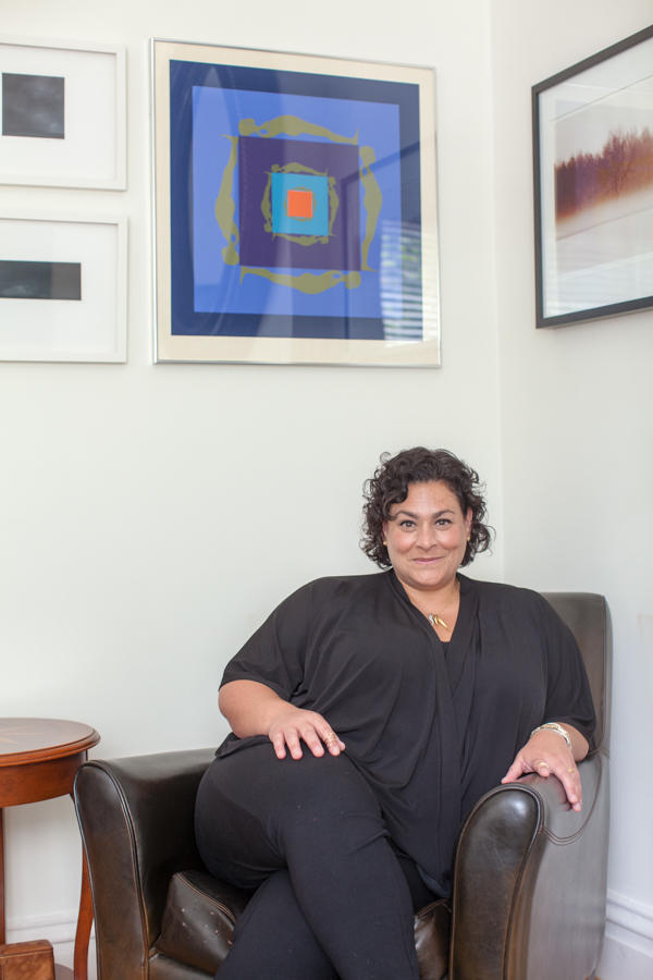 Lisa Melandri seated beneath a Trova print