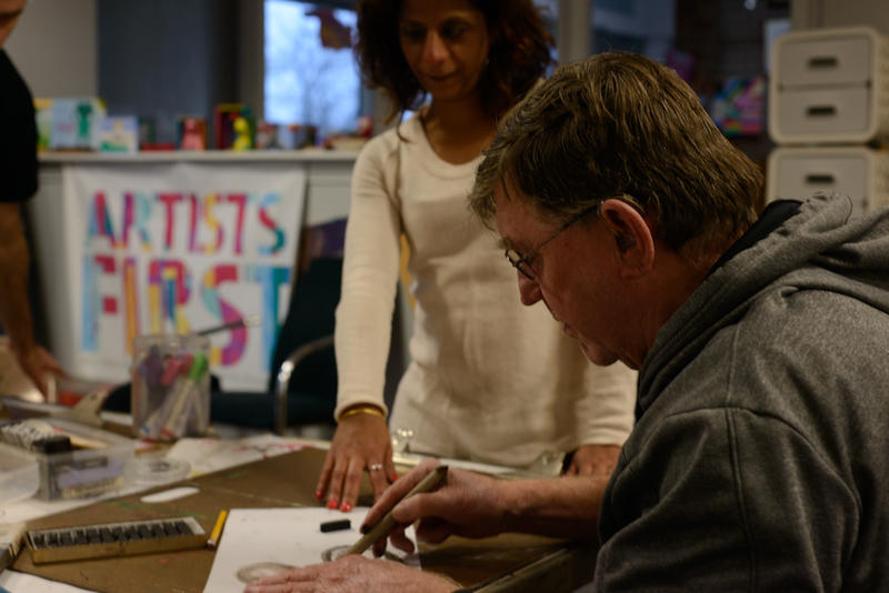 Artists First executive director Sheila Suderwalla helps Vietnam veteran Mike David with a charcoal project.