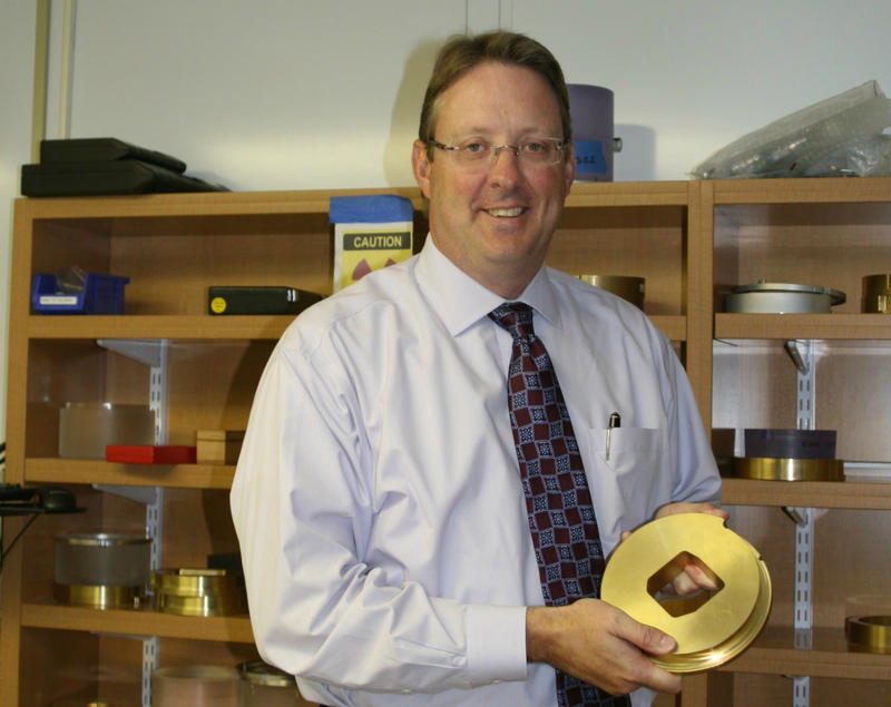 Jeffrey Bradley holds a brass aperture for use in proton therapy.
