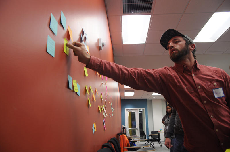 Marcis Curtis, an artist and co-founder of Citizen Carpentry, organizes sticky notes during a brainstorming session at the Community Reaction Lab.
