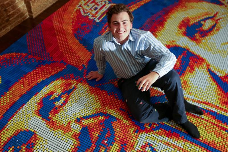 Connor Wright seated on his trio of Stan Musial portraits at Ballpark Village. Wright used 5,980 Rubik's Cubes to make the piece.