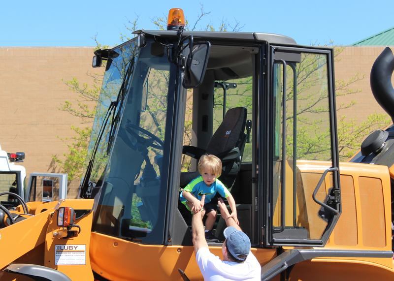 Two-year-old Jack Hennessy of Crestwood climbs out of the cab of a bulldozer and into the arms of his dad, Kevin, who used to come to Crestwood Plaza when he was his son's age.