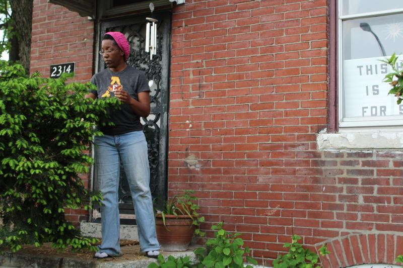 """Sheila Rendon outside her home in the St. Louis Place neighborhood. A sign in the window says """"This home is not for sale."""""""