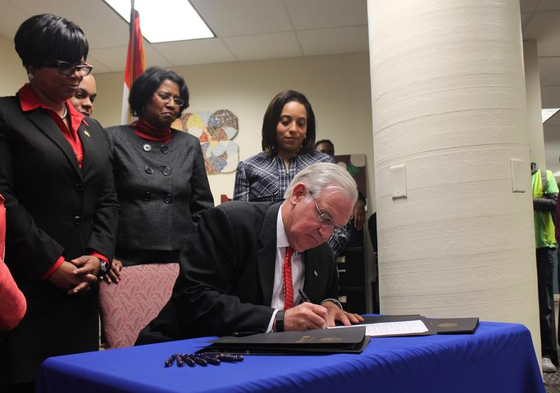 "Missouri Gov. Jay Nixon signs an executive order  ""banning the box"" on state job applications at the office of the St. Louis Agency on Training and Employment."