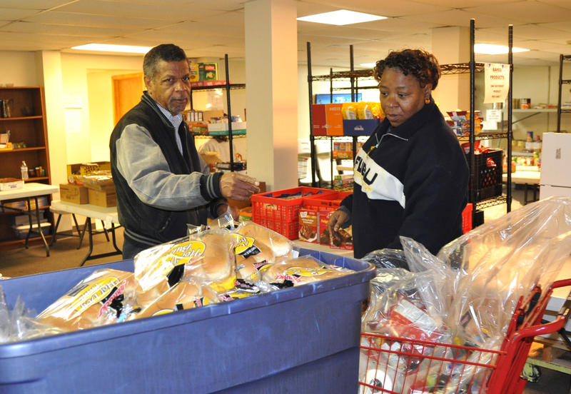 Sam Johnson, left, assists a visitor at the food pantry he manages for St. Elizabeth, Mother of John the Baptist Church, in north St. Louis.