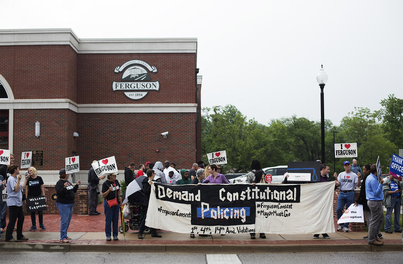 Attendees for both a welcome rally for Ferguson's new police chief, Delrish Moss, and a protest against the city's attorney, Stephanie Karr, demonstrate outside the Ferguson Police Department on May 9, 2016.