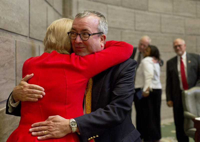Sen. Joe Keaveny receives a hug while walking out of the Senate chamber on Friday. Keaveny announced he will resign from the senate to become an administrative law judge.