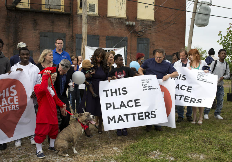 "Outside the old Buster Brown factory, party attendees hold up signs and pose for photos as part of the ""This Place Matters"" campaign, a social media project started by the National Trust for Historic Preservation."