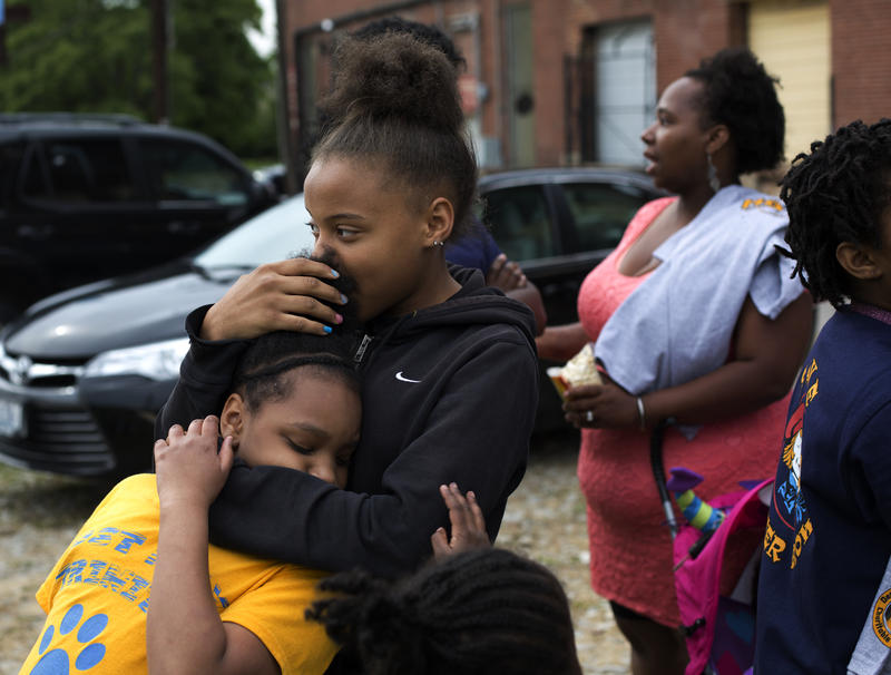 Kirsten Wright, 14, hugs her younger sister, Jounrey Moore, 9, at Jim Osher's Buster Brown party. The sisters live just outside the proposed NGA footprint.