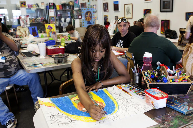 Priscilla Miller, who has been coming to Artists First for about a year, colors in one of her drawings.