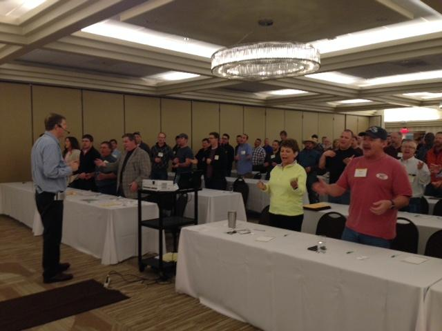 Paul Dewees, president of the Missouri Auction School, leads students in the daily warm-up, taking them through tongue-twisters and dollar drills.