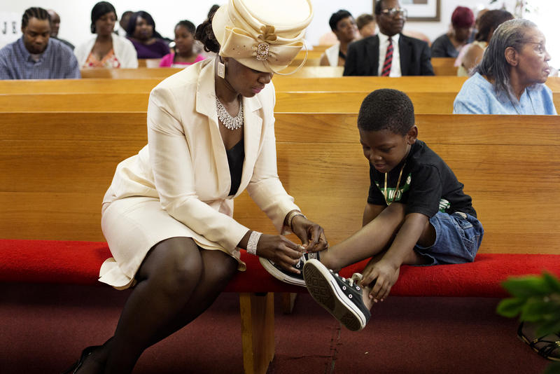 Felicia Davis, wife of the Rev. Jonathan Davis, helps a church member's son with his shoelace.
