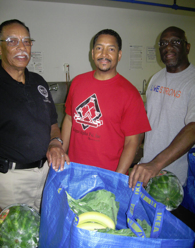 Herman Smith, Bryant Kirby and Robert Redmond hold a sack of produce for distribution to coop members.
